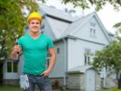 Smiling manual worker in helmet with hammer — Stock Photo