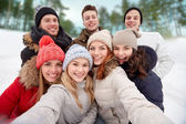 Group of smiling friends taking selfie outdoors — Stock Photo