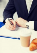 Businessman with coffee writing something — Foto de Stock