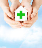 Hands holding paper house with green cross — Stock Photo
