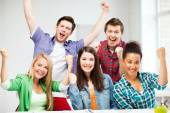 Students holding hands up at school — Stock Photo
