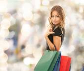 Young happy woman with shopping bags over lights — Foto de Stock