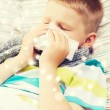 Ill boy blowing nose with tissue at home — Stock Photo #63930465