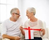 Gelukkig senior koppel met de doos van de gift thuis — Stockfoto