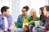Alunos se comunicando e rindo na escola — Fotografia Stock