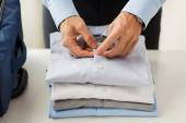 Businessman packing clothes into travel bag — Stock Photo