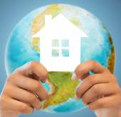 Couple hands holding green house over earth globe — Stock Photo
