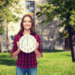 Young woman in casual clothes with wall clock — Stock Photo #64073577