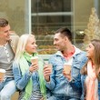 Group of smiling friends with take away coffee — Stock Photo #64077489