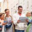 Group of friends with city guide, map and camera — Stock Photo #64077589
