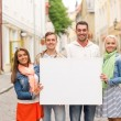 Group of smiling friends with blank white board — Stock Photo #64077857