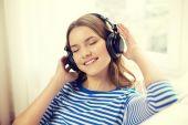 Usměvavá mladá dívka v domácí sluchátka — Stock fotografie