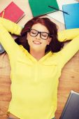 Smiling student in eyeglasses lying on floor — Stock Photo