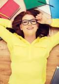 Smiling student in eyeglasses lying on floor — Stock Photo