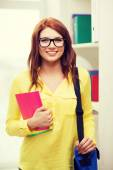 Smiling female student with bag and notebooks — Stock Photo