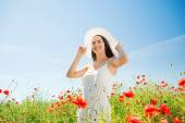 Smiling young woman in straw hat on poppy field — Stock Photo