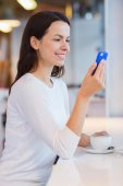 Smiling woman with smartphone and coffee at cafe — Stock Photo