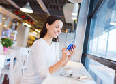 Smiling woman with smartphone and coffee at cafe — Foto de Stock
