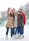 Glückliche Freunde mit Smartphone auf Eisbahn — Stockfoto