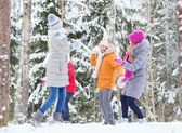 Group of happy friends playing snowballs in forest — Stock Photo