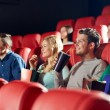 Happy friends watching movie in theater — Stock Photo #64246341