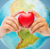 Woman hands holding red heart over earth globe — Stock Photo