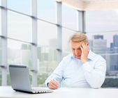 Senior man with laptop and pen writing at office — Stock Photo
