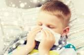 Sjuk pojke blåser näsan med vävnad hemma — Stockfoto
