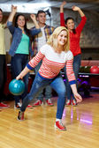 Happy young woman throwing ball in bowling club — Stock Photo