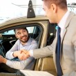 Happy man with car dealer in auto show or salon — Stock Photo #64623621