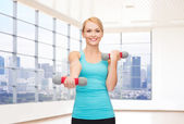 Smiling woman with dumbbells flexing biceps in gym — Stock Photo