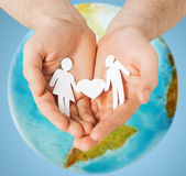 Human hands holding paper couple over earth globe — Stock Photo