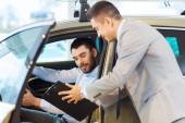 Happy man with car dealer in auto show or salon — Stock Photo