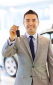 Happy man showing key at auto show or car salon — Zdjęcie stockowe