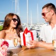 Smiling couple with gift box cafe — Stock Photo #64756503
