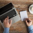 Close up of male hands with laptop and notebook — Stock Photo #64756639