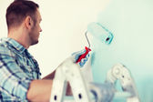 Close up of male in gloves holding painting roller — Stock Photo