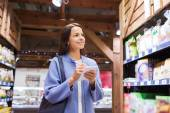 Happy woman with notepad in market — Stock Photo