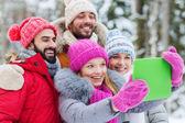 Lachende vrienden met tablet pc in winter forest — Stockfoto