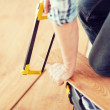 Close up of male hands cutting parquet floor board — Stock Photo #64848653
