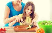 Menina a sorrir com mãe cortar pepino — Fotografia Stock