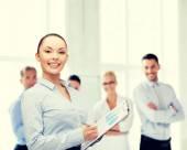 Joven empresaria sonriente con portapapeles y pluma — Foto de Stock