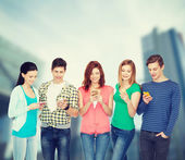 Smiling students with smartphones — Stock Photo