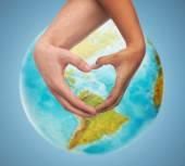 Human hands showing heart shape over earth globe — Stock Photo