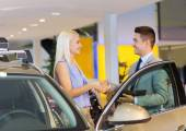 Happy woman with car dealer in auto show or salon — Foto Stock