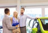 Happy couple with car dealer in auto show or salon — Stock Photo