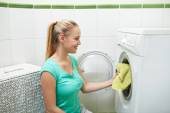 Happy woman putting laundry into washer at home — Stock Photo