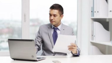 Smiling businessman with laptop and papers — Vídeo de Stock