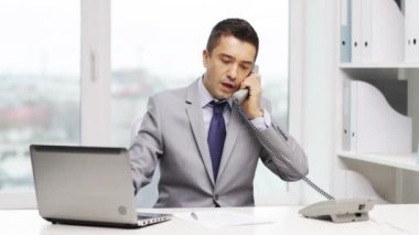 Smiling businessman with laptop calling on phone — Stock Video