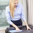 Businesswoman packing things in suitcase — Stock Photo #65165419